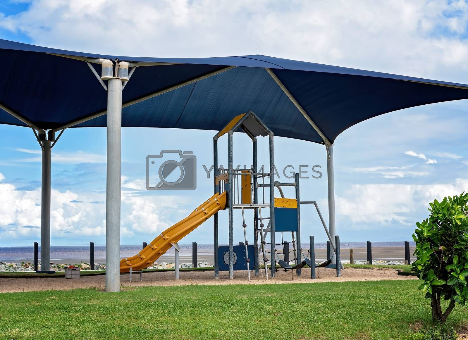 A beachfront shaded children's playground with climbing frame and slipper slide