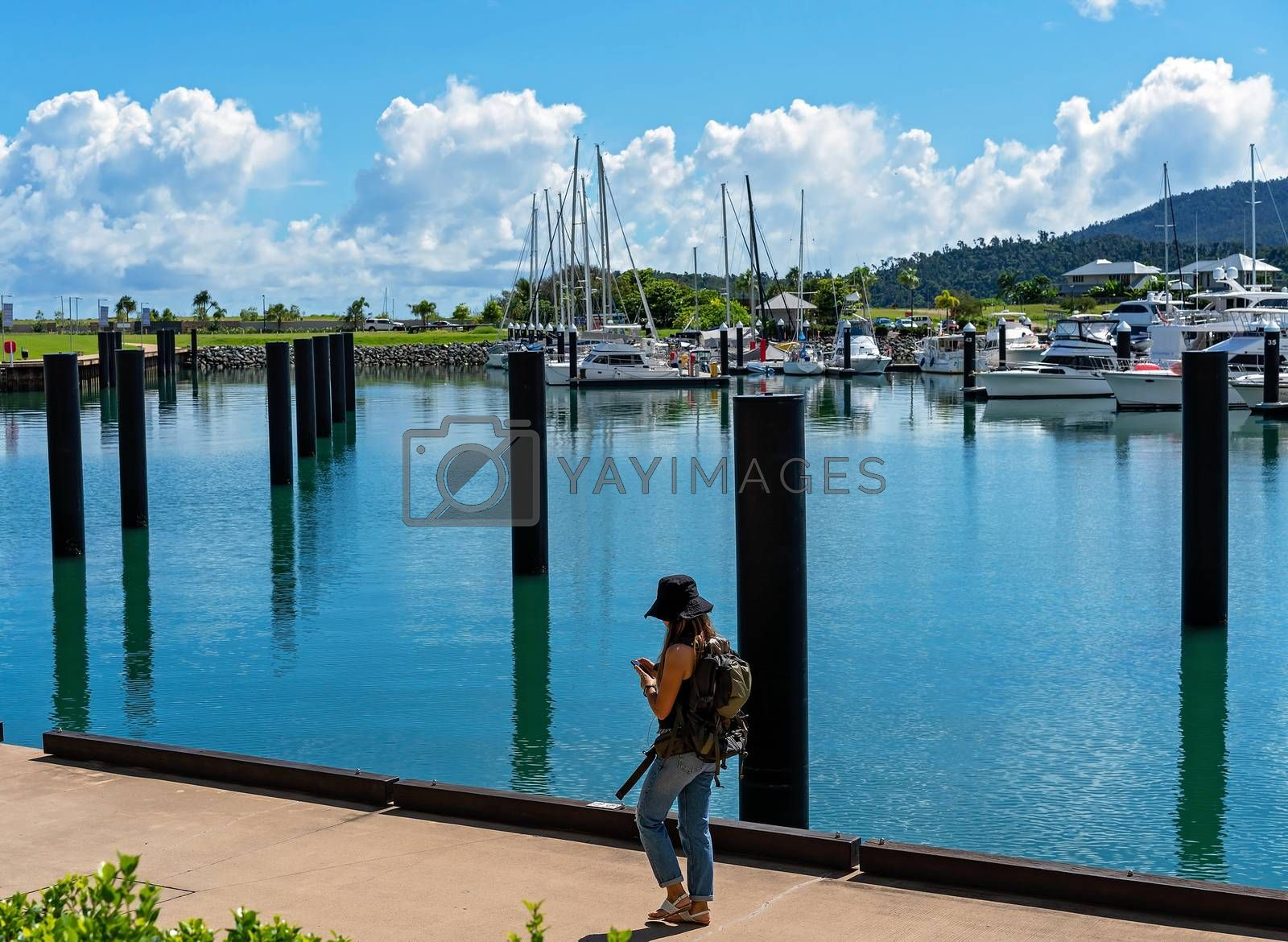A young unidentifiable female backpacker walking beside a marina looking at her phone, oblivious to the beautiful scenery