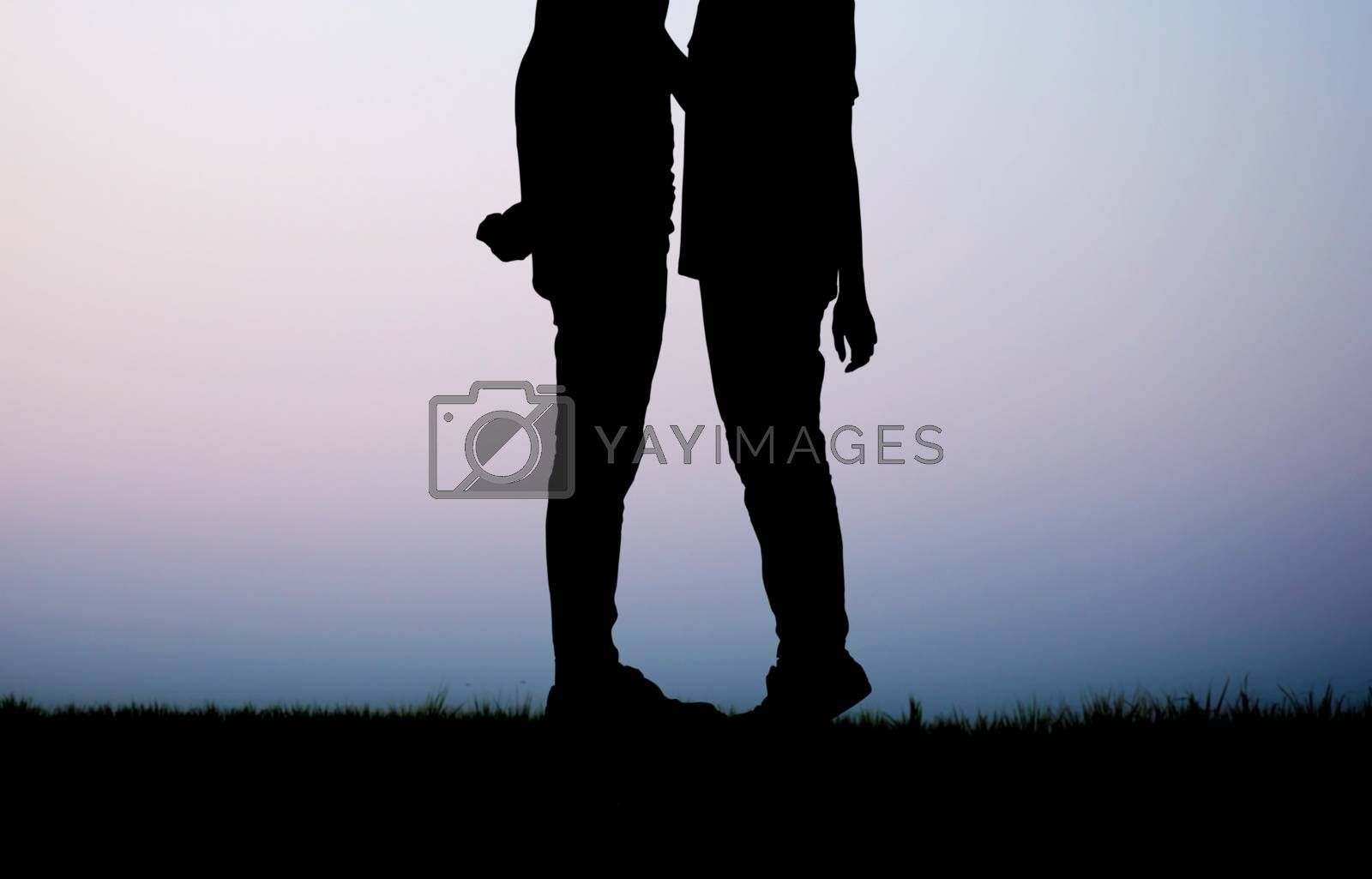 Couple on field with the silhouette at sky.