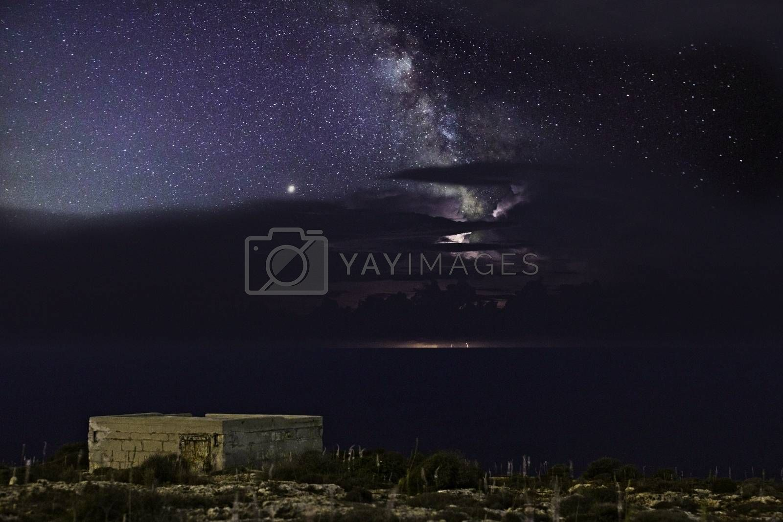 The Milky Way rises from behind a distant storm cell over the horizon