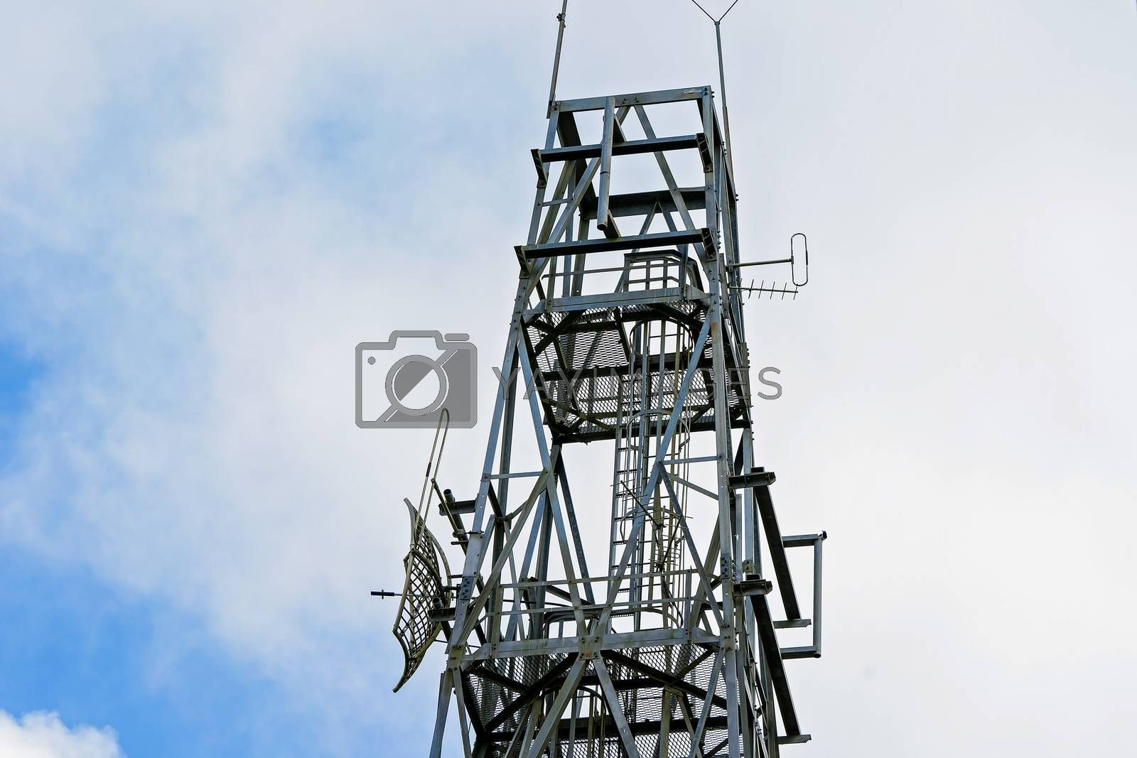 Modern technology communication towers against a cloudy blue sky
