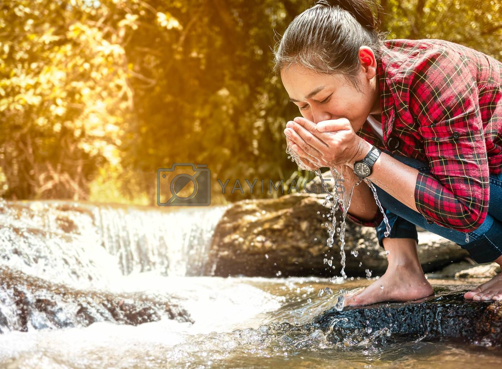 Woman catches running pure water in her cupped hands at waterfall. Conservation of natural resources.