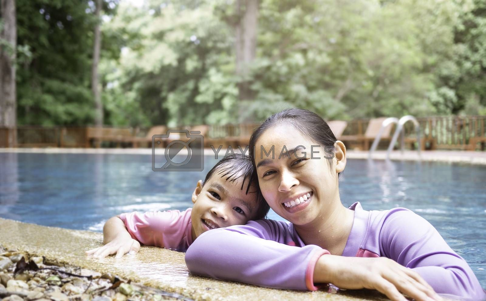 Happy young mother and her daughter smiling in swimming pool in a hot summer day. Family lifestyle in vacation.