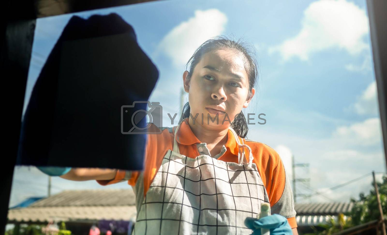 Woman wearing protective gloves cleaning window by spraying cleaning products and wiping with blue rag. Cleaning House concept.