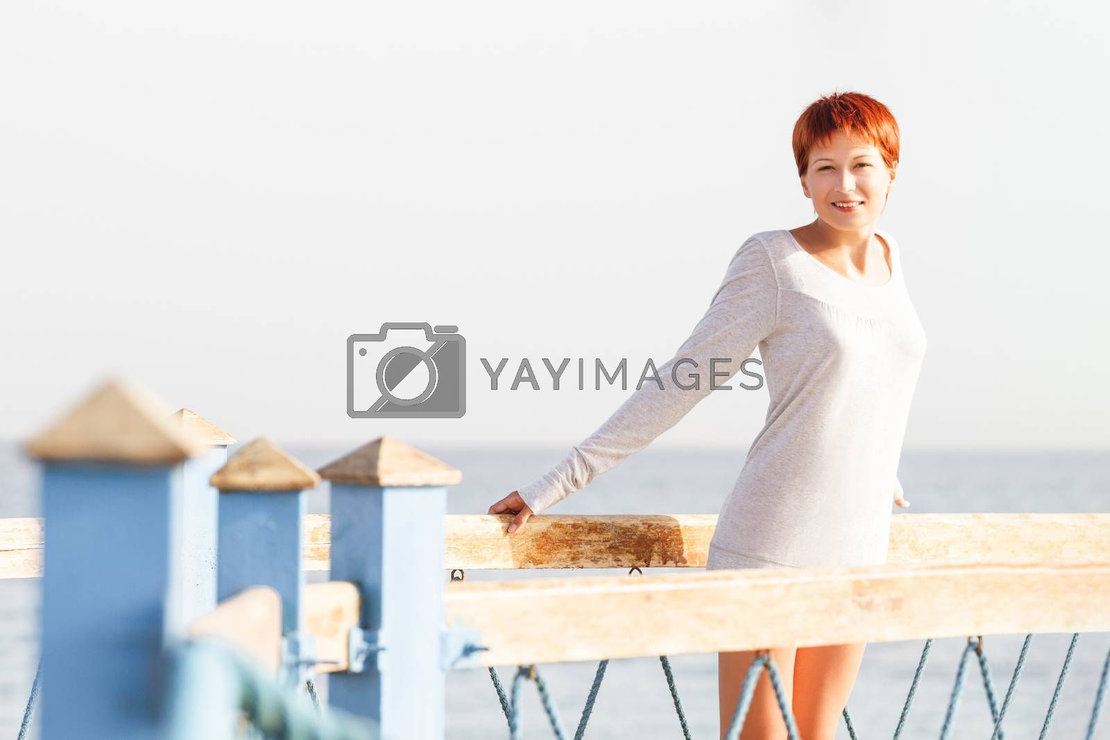 Wide smiling young woman with red short hair cut stays on wooden pier. Coastal morning sunlight. Natural beauty.