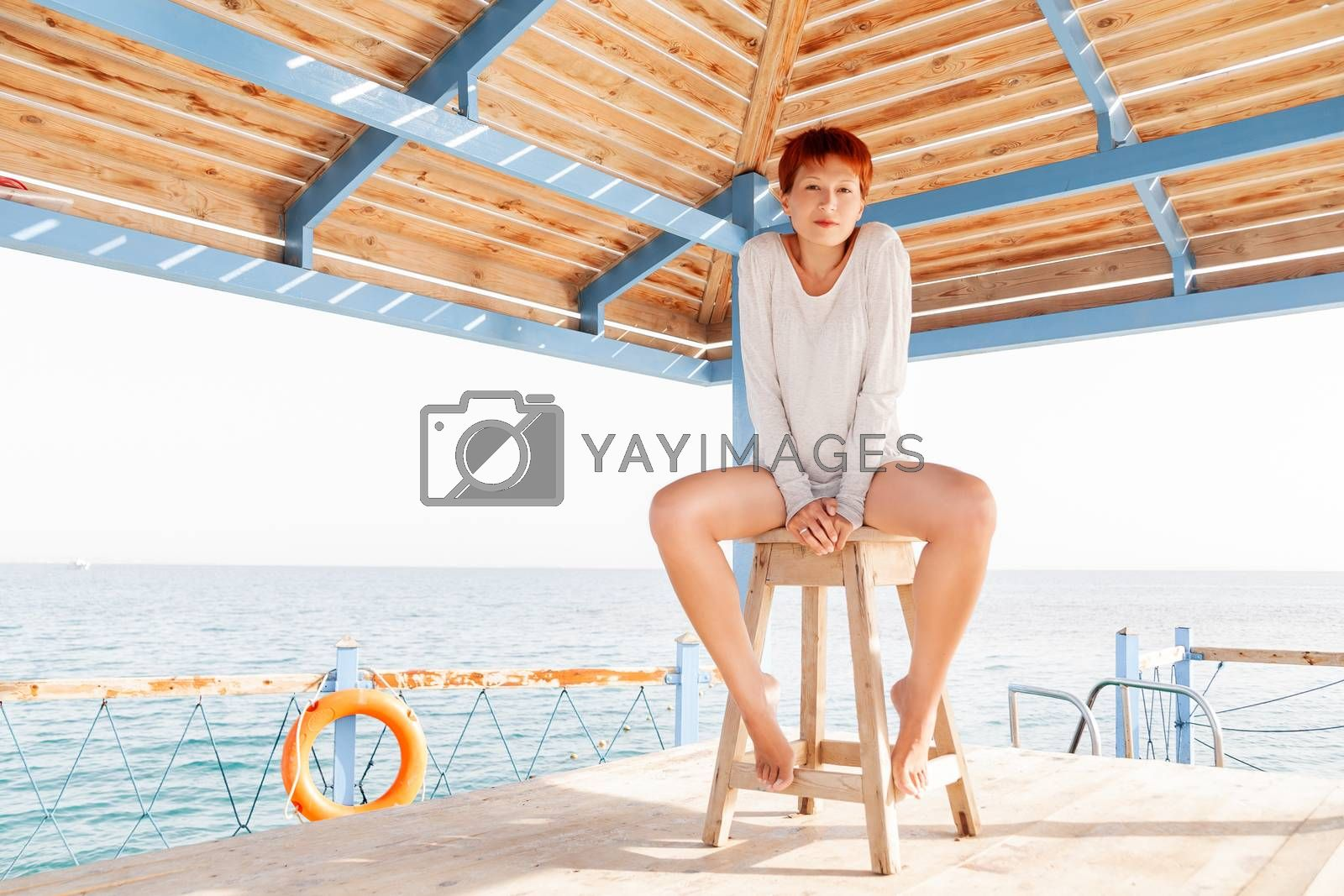 Young woman with red short hair cut sits on wooden pier at lifeguard's place. Coastal morning. Natural beauty.