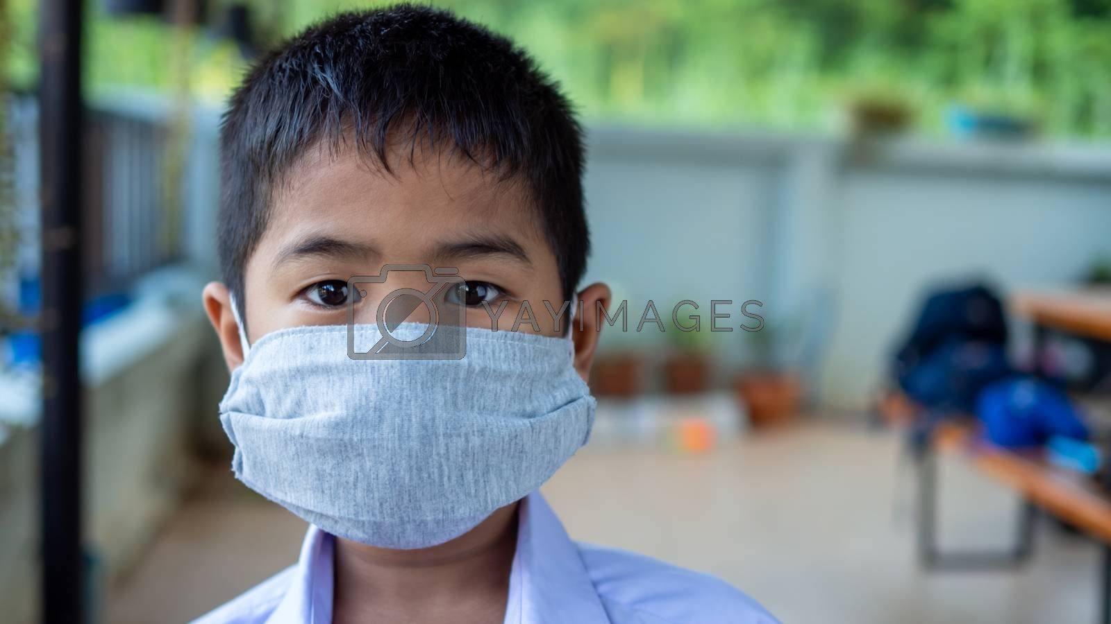 Close-up portrait of a cute boy wearing a protective mask and he by Unimages2527