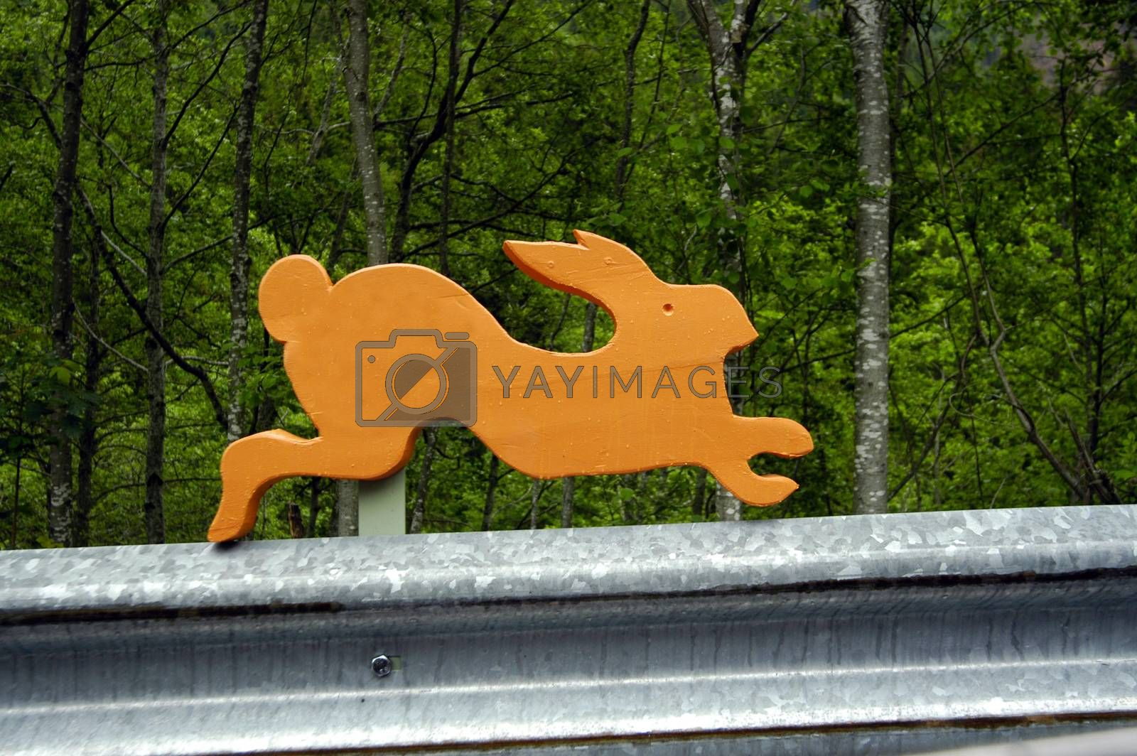 symbol of a wooden rabbit on a guard rail on the street