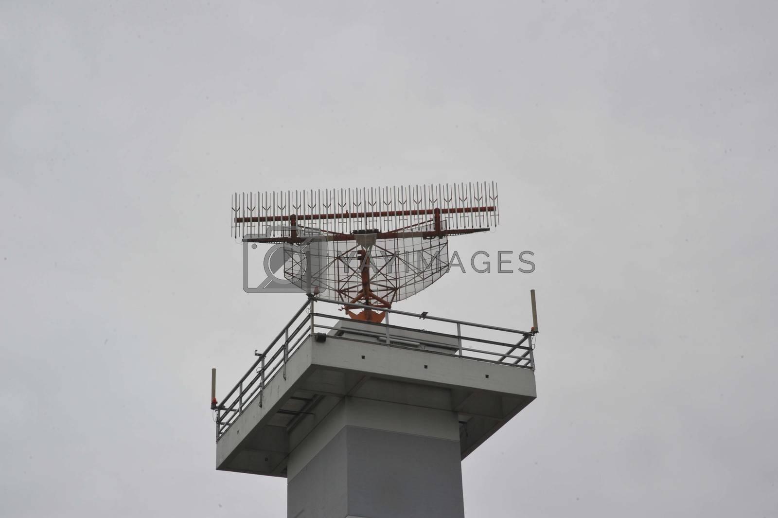 an air traffic control tower with radar, grey sky background