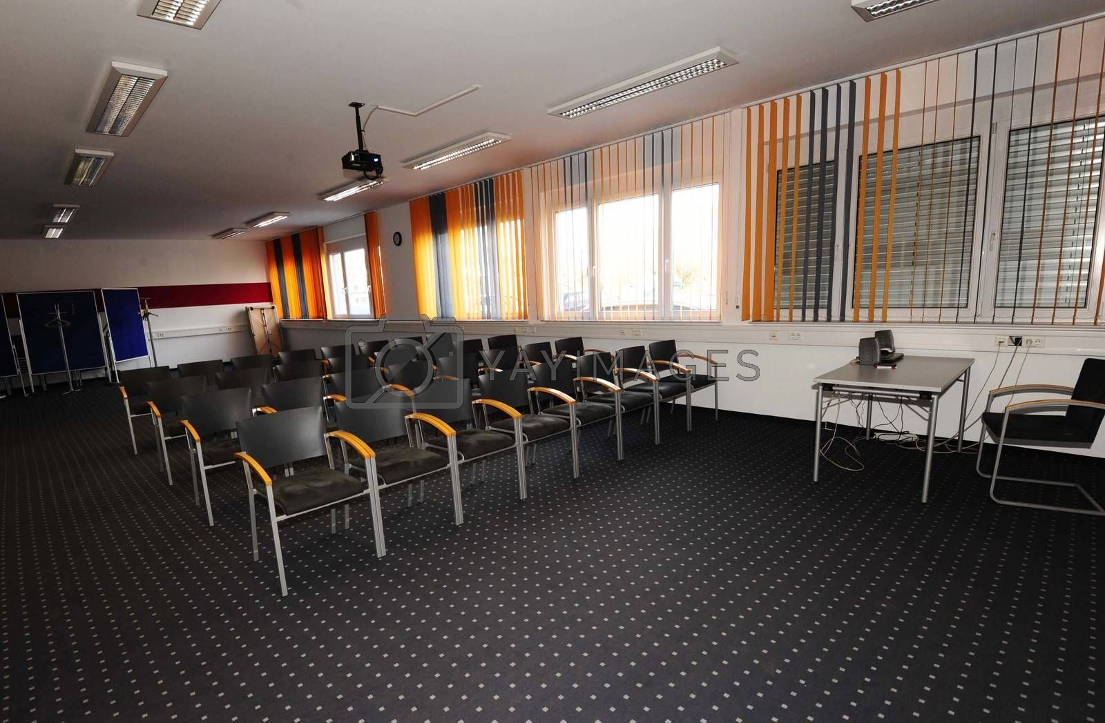 empty seminar room with chairs, projector, desk and windows for training people