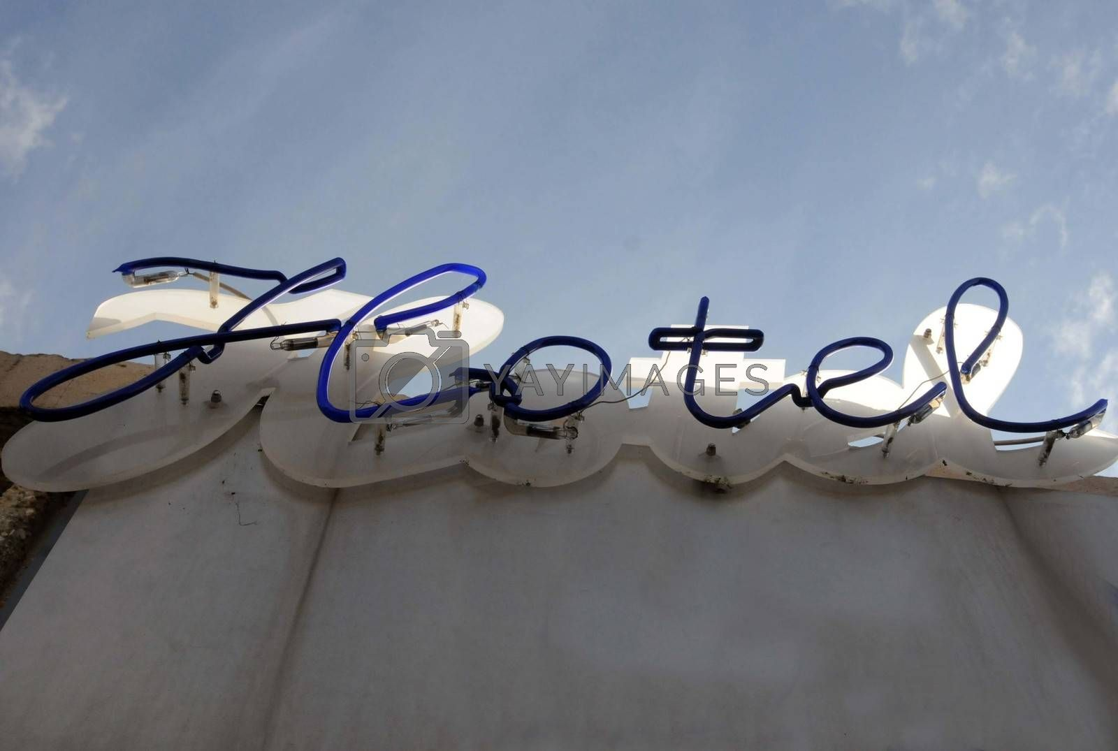 a Hotel sign on a wall with blue sky in the background