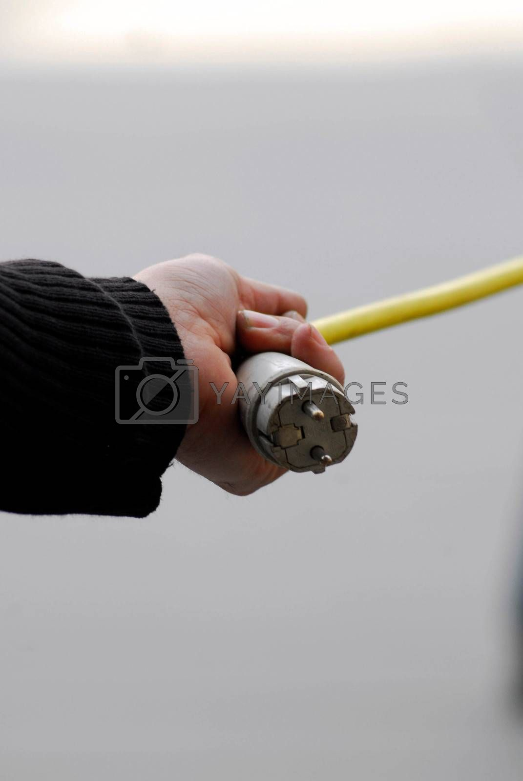 man holding a 220 volt power plug with yellow cable