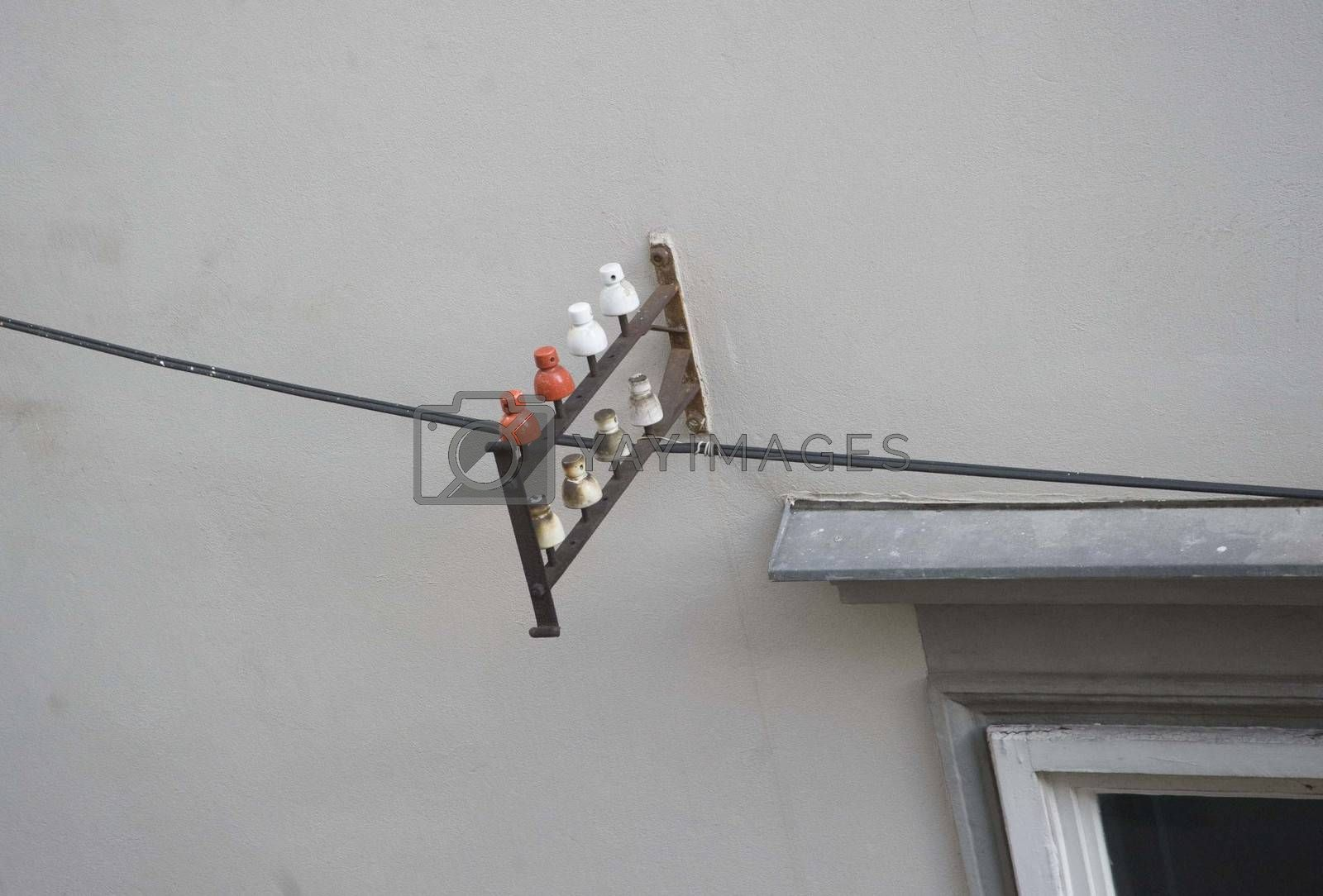 a ceramic insulator mounted on the wall of a building