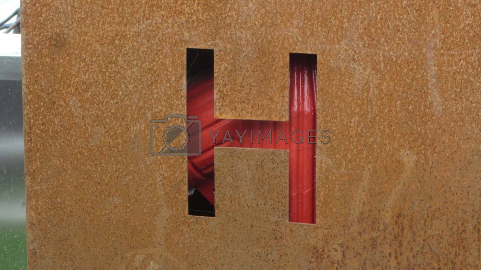 The letter 'H' cut in a rusty old metal plate