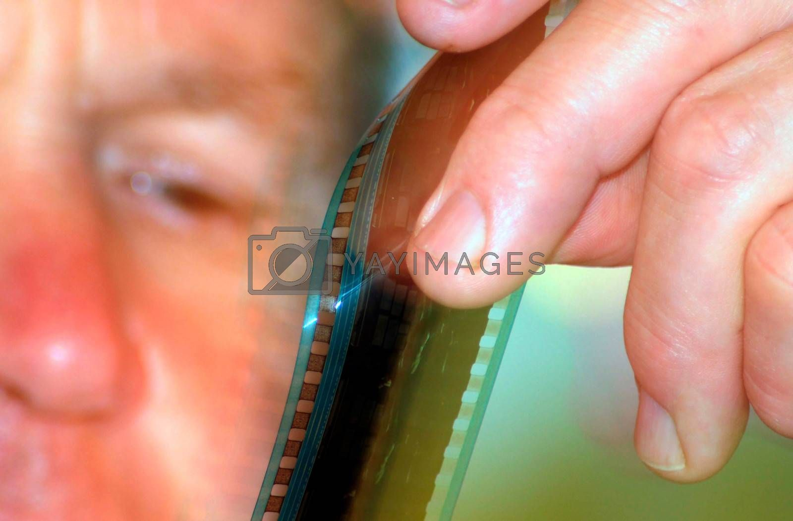 film projectionist in a cinema looking at a filmstrip in his hand