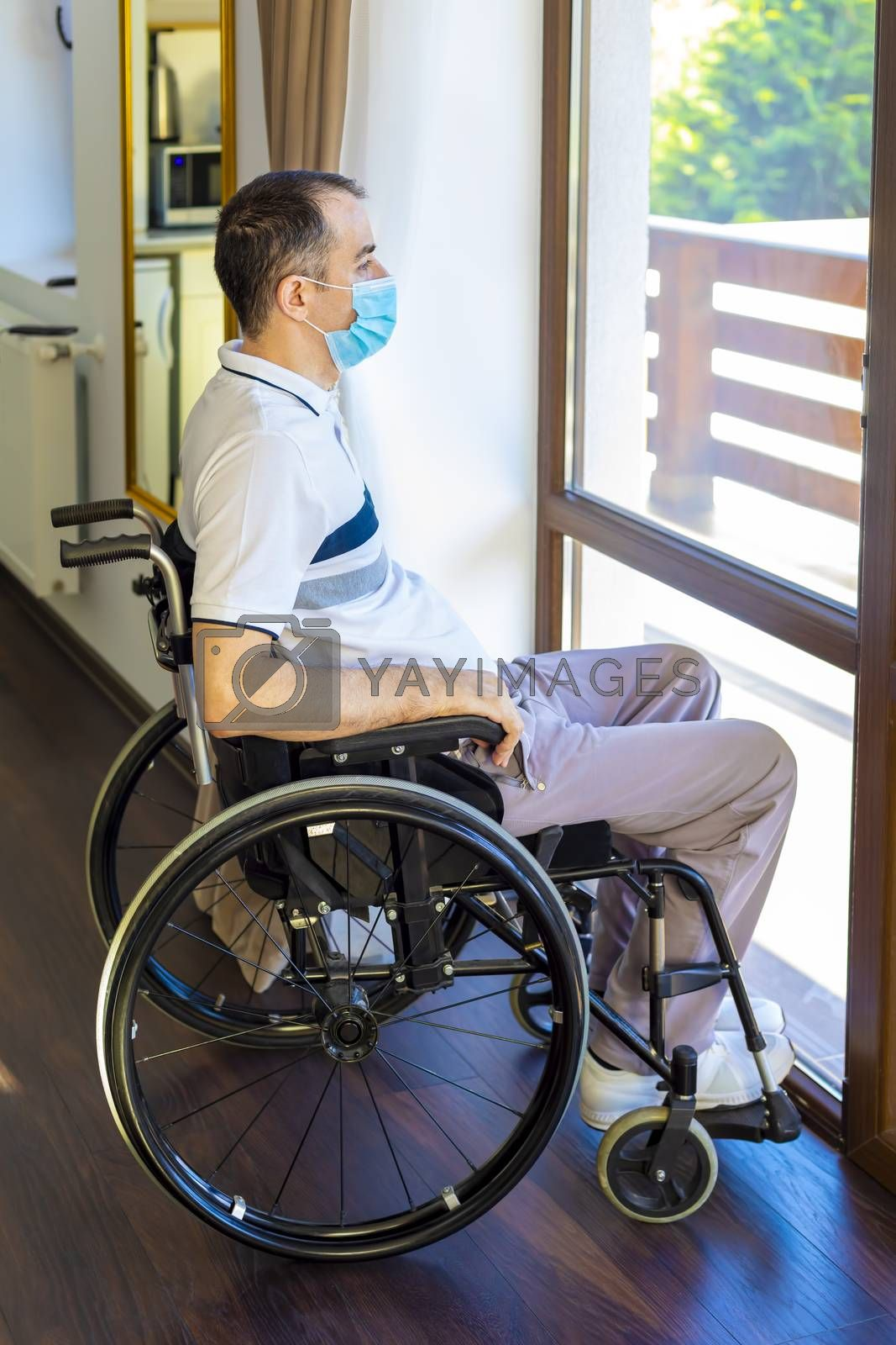 Lonely young man wearing face mask sitting in a wheelchair alone looking out the window. Focus on his face.