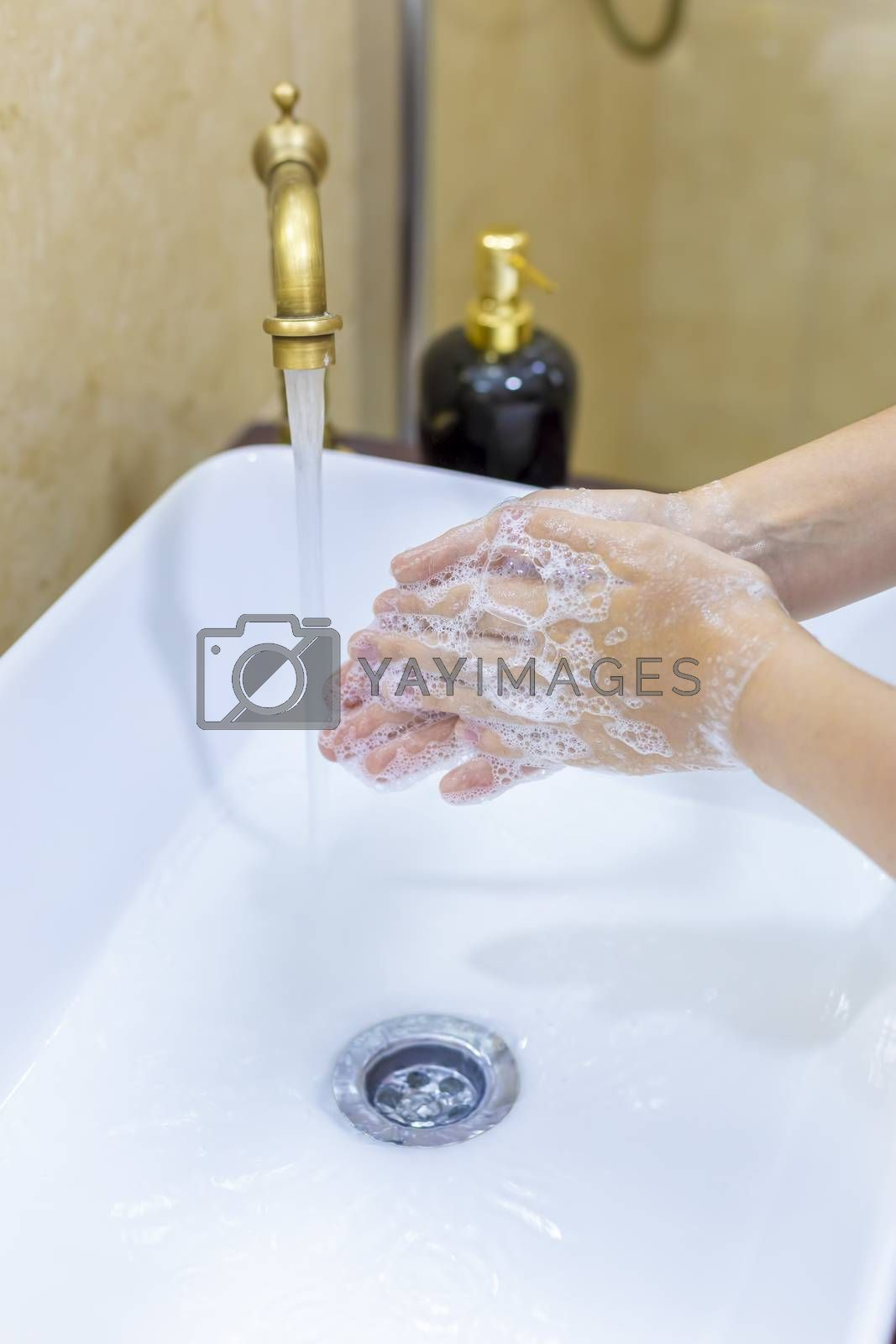 Woman washing and disinfecting hands with soap and hot water as part of coronavirus prevention and protection protocols; stop spreading covid-19 hygiene protocols. Focus on her finger.