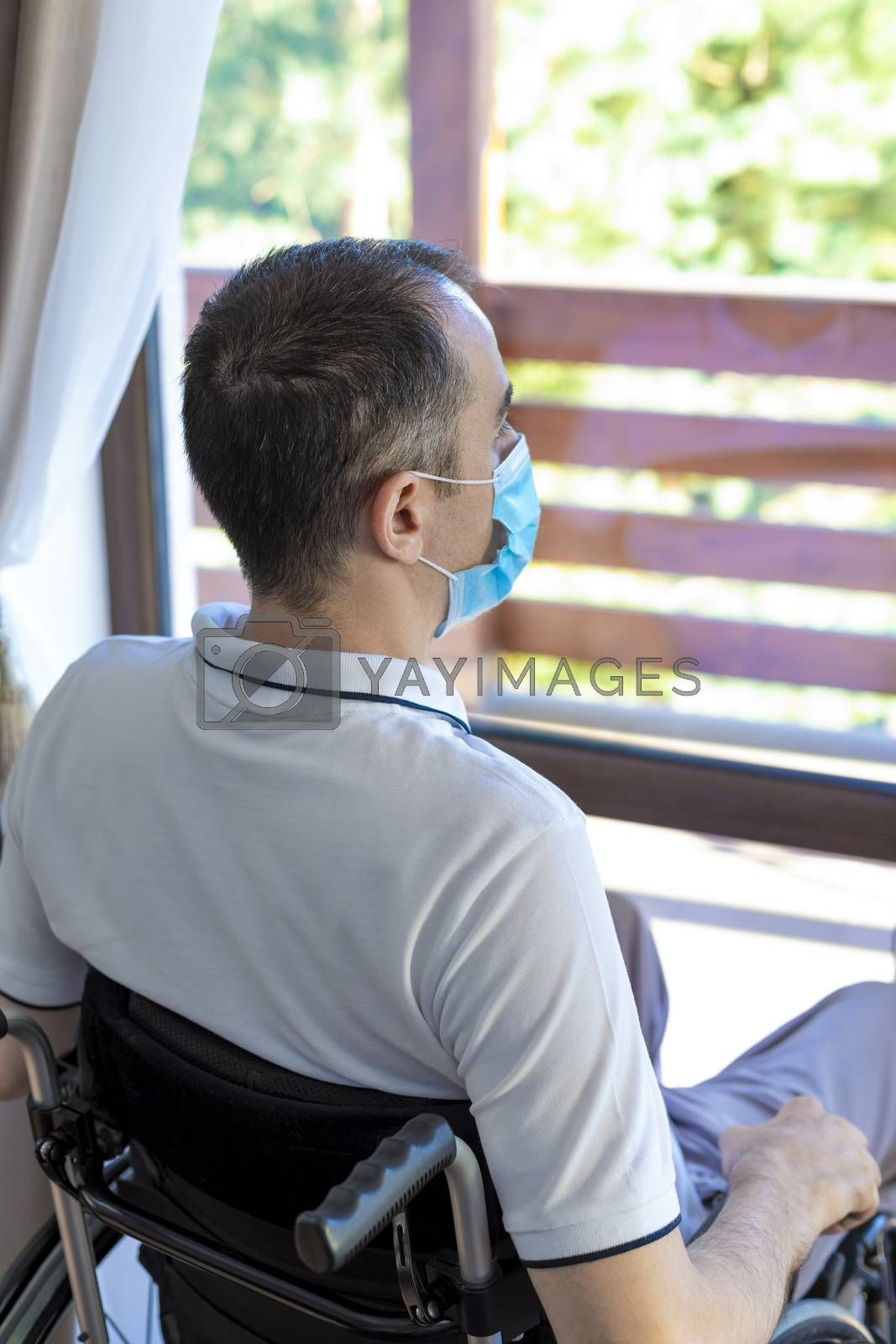 Lonely young man wearing face mask sitting in a wheelchair alone looking out the window. Focus on his head.