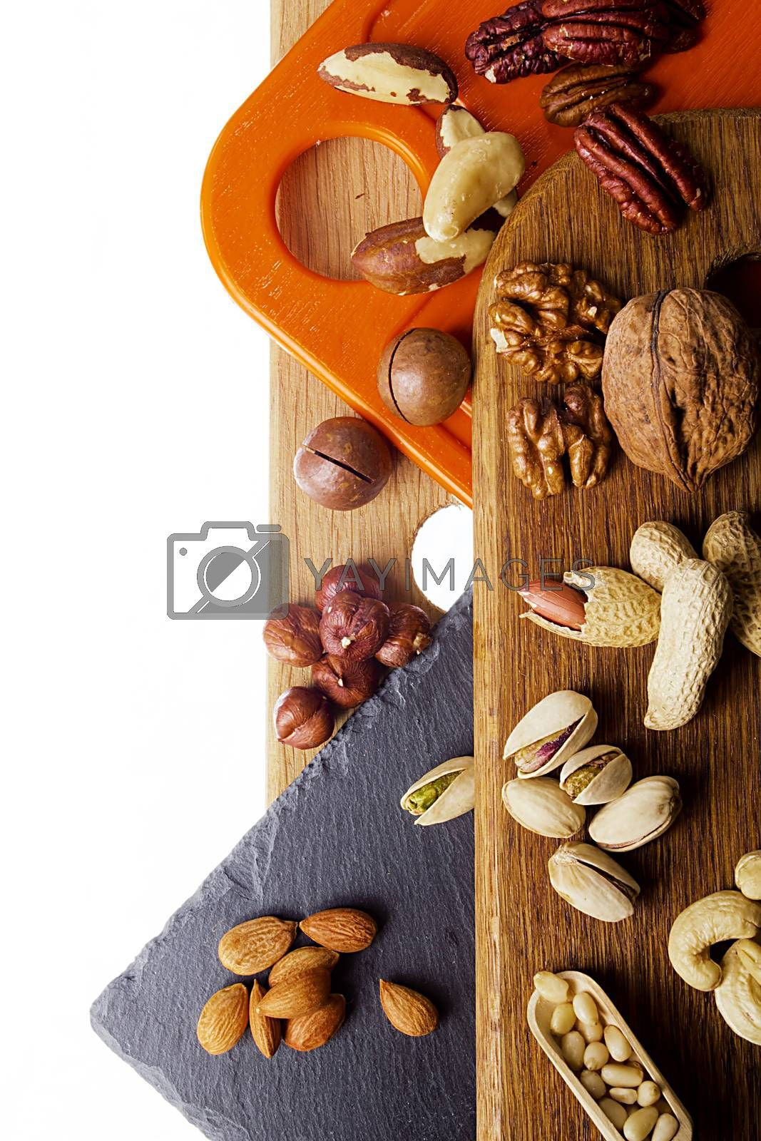 Mix of nuts on different cutting boards on a white background