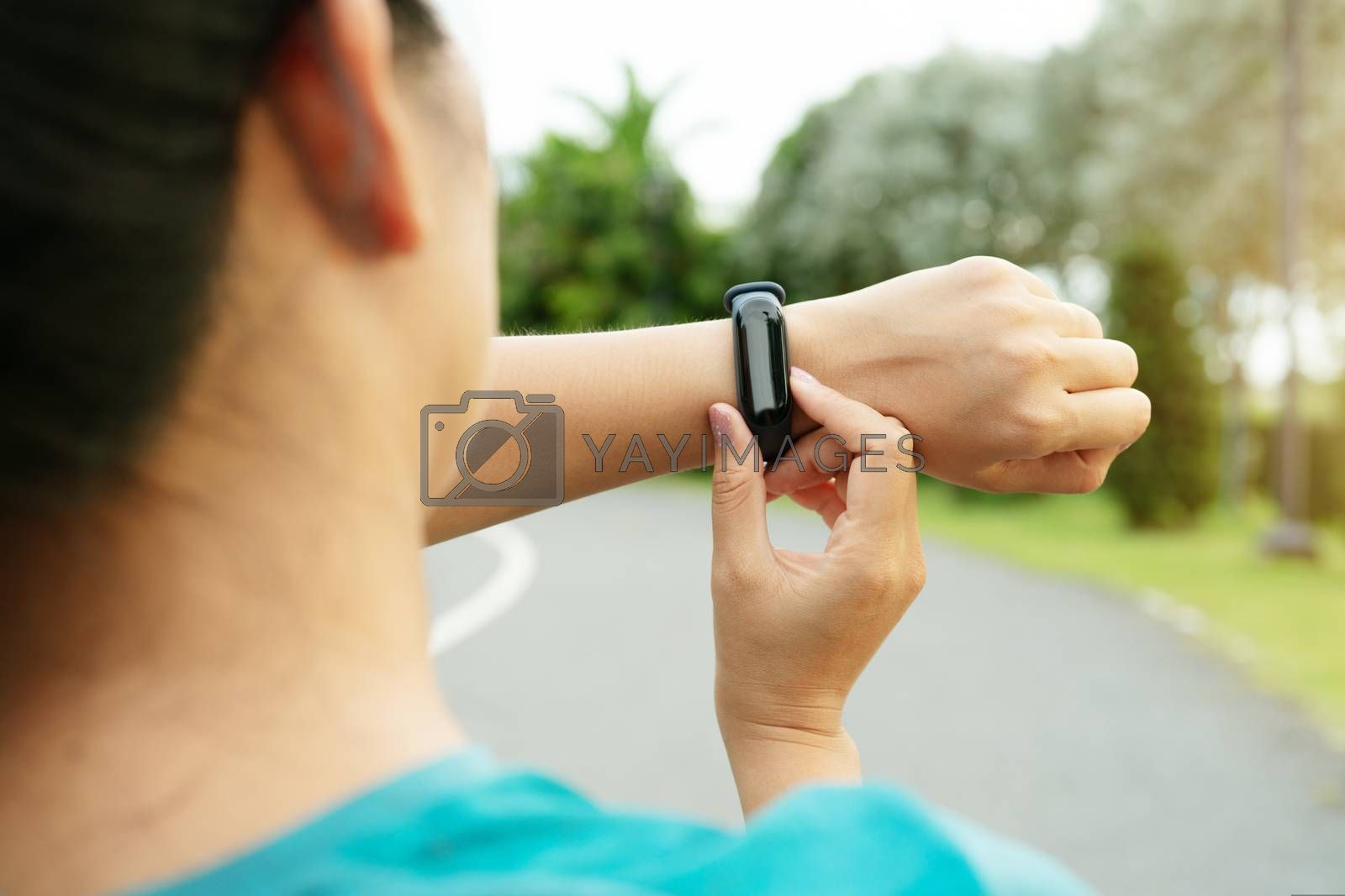 fitness woman runner setting up smart watch before running. Outdoor exercise activities
