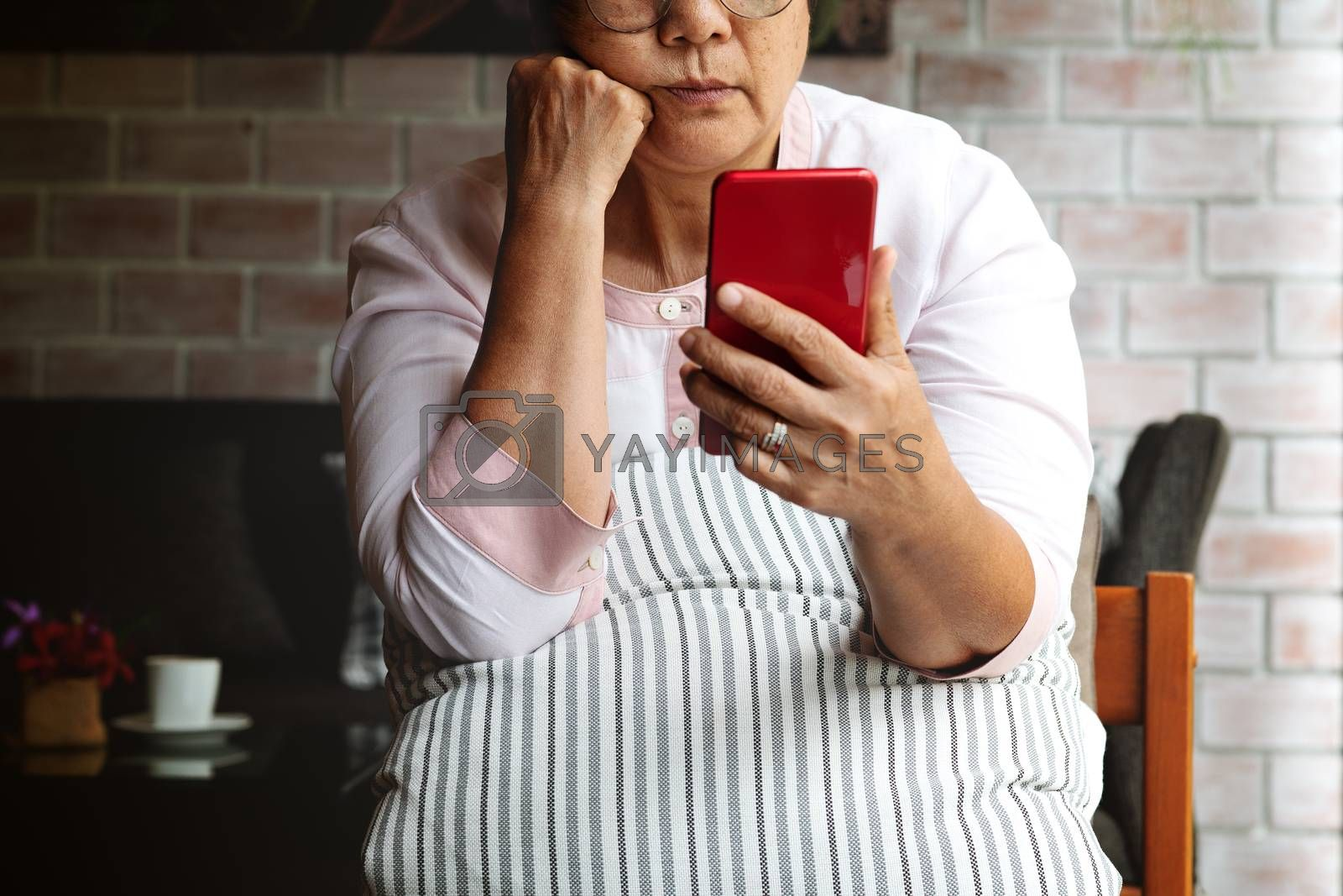 Frustrated older mature woman feeling boring desperate looking on the smartphone, stressed sad middle aged female depressed by hearing bad news