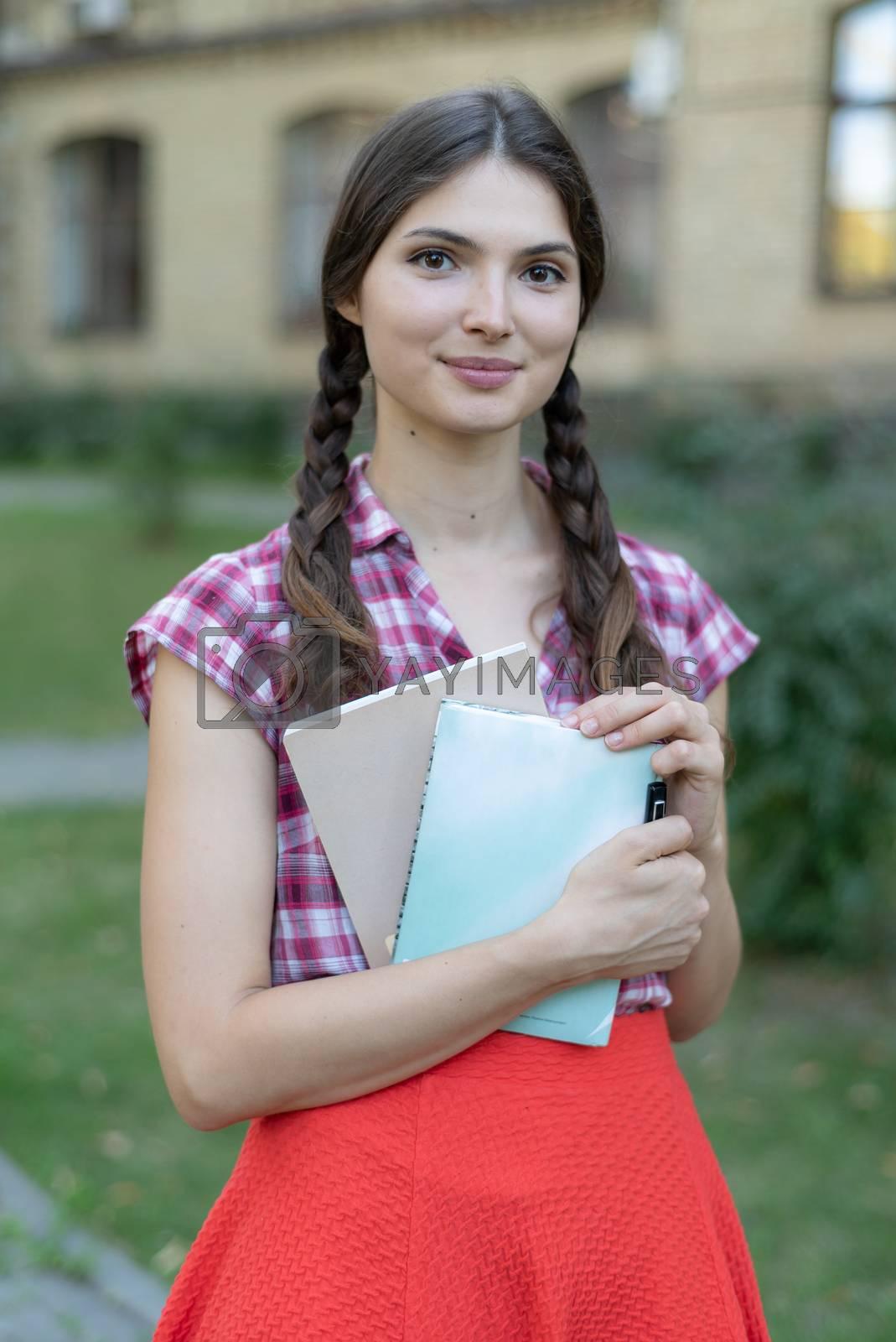 Girl student in red skirt and plaid shirt. Kyiv. Ukraine