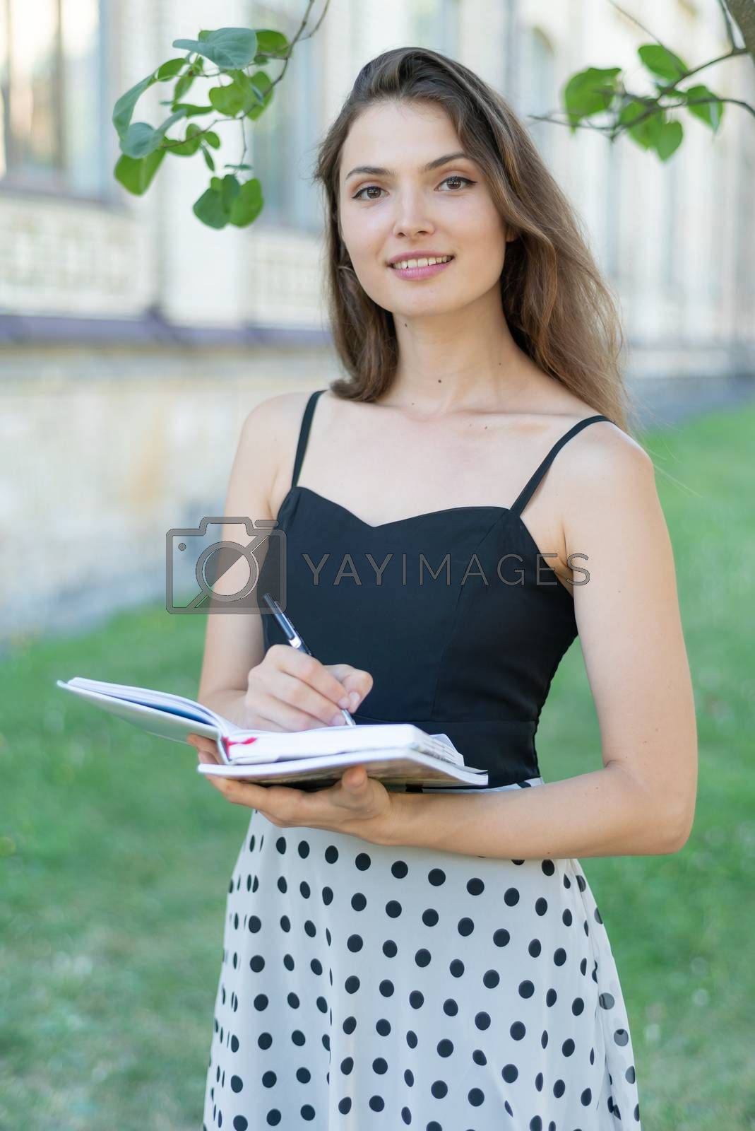 Young girl student with book and notebook