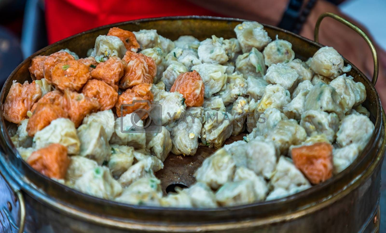 'Shumai' (Shaomai) or Kanom Jeeb' a 'Dim Sum' Chinese traditional steamed dumplings food with shrimp and pork inside in metal tray for sale at street market. Traditional breakfast asian styles. Selective focus.