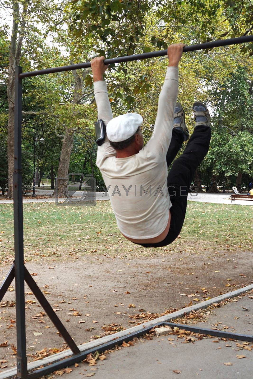 man is engaged on a horizontal bar in the park.