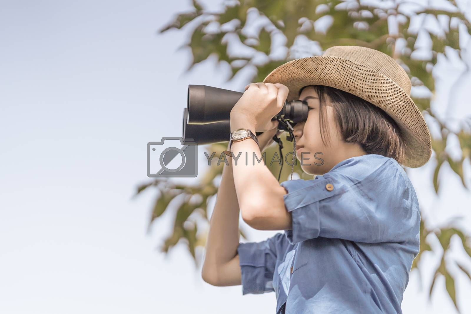 Close up Young asian woman short hair wear hat and hold binocular in grass field countryside Thailand