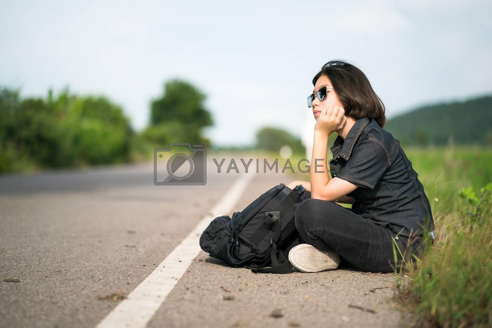 Young asian woman short hair and wearing sunglasses sit with backpack hitchhiking along a road wait for help in country road Thailand