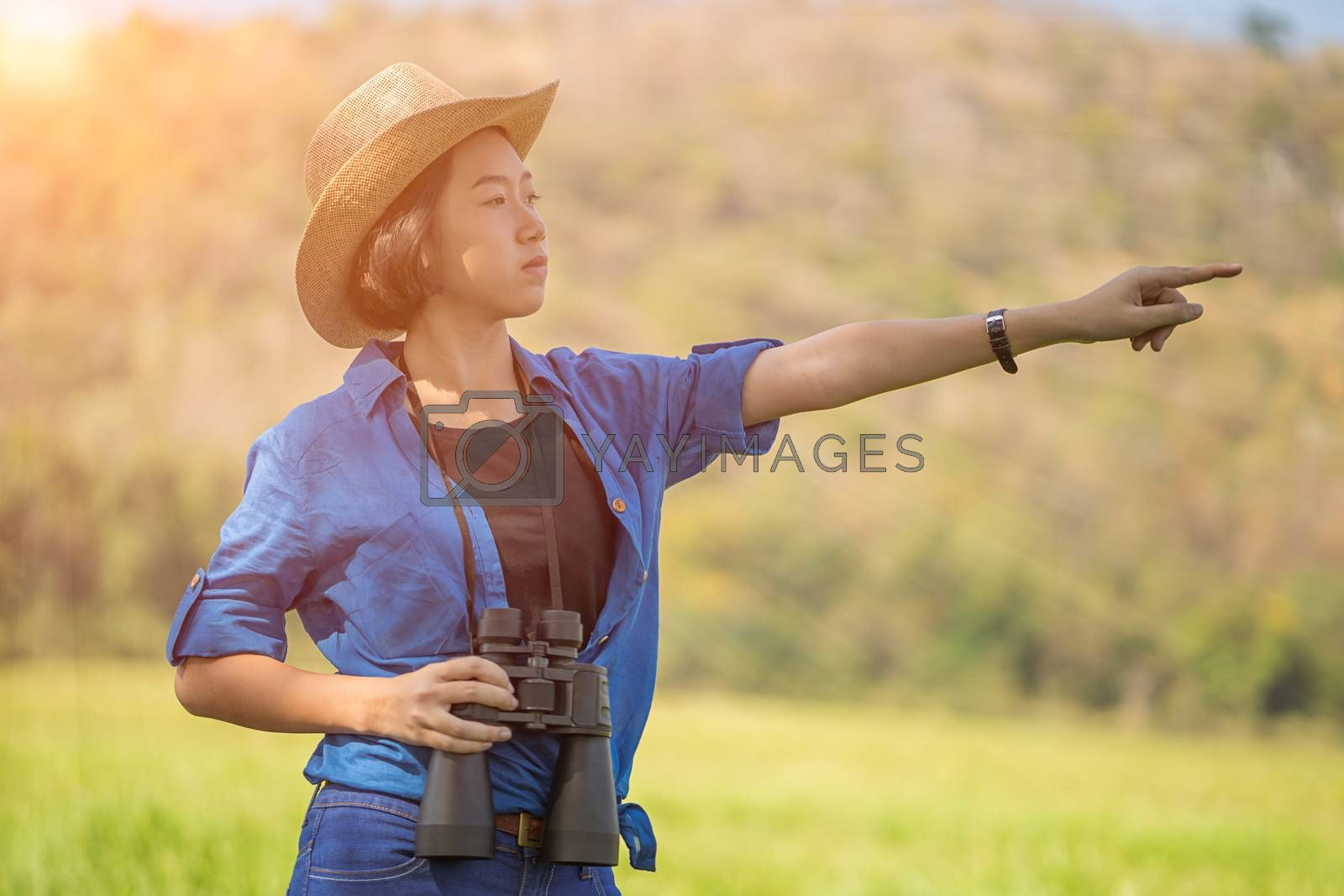Young asian woman short hair wear hat and hold binocular in grass field countryside Thailand
