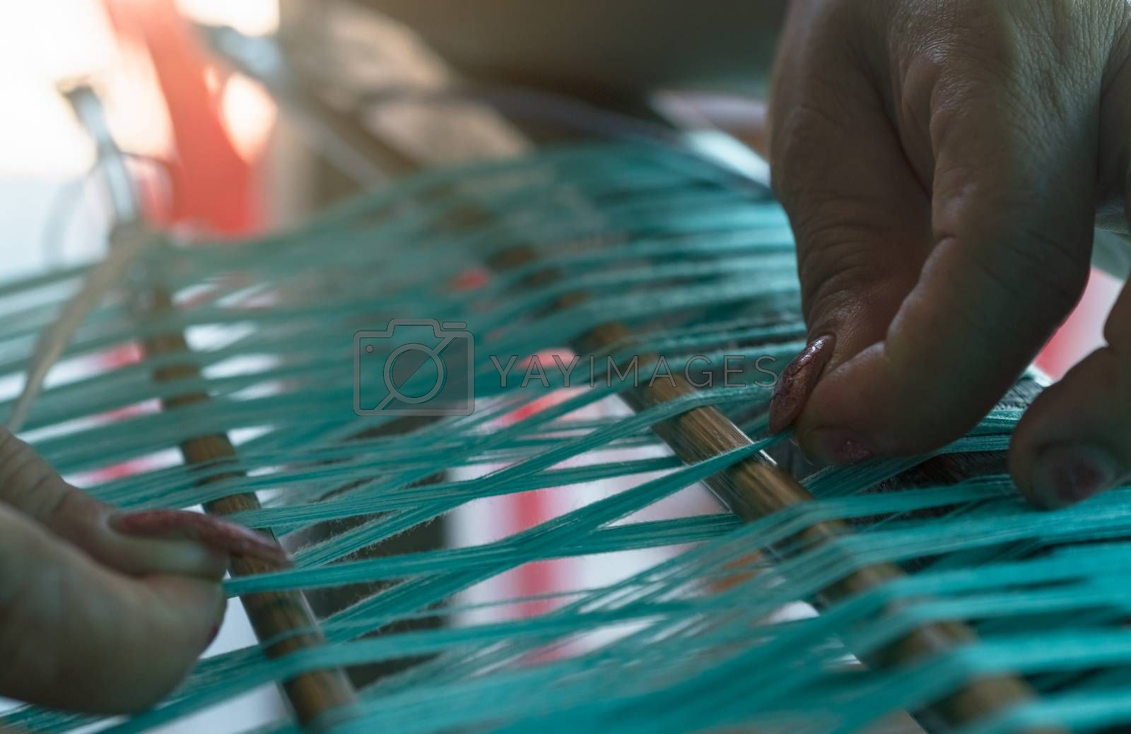 Woman working on weaving machine for weave handmade fabric. Textile weaving. Weaving using traditional hand weaving loom on cotton strands. Textile or cloth production in Thailand. Asian culture.