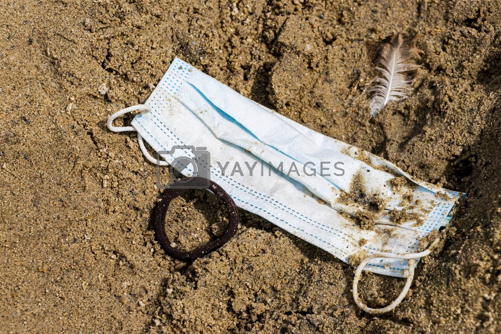 Dirty trash surgical masks on beach sand in nature. Corona virus pollution.