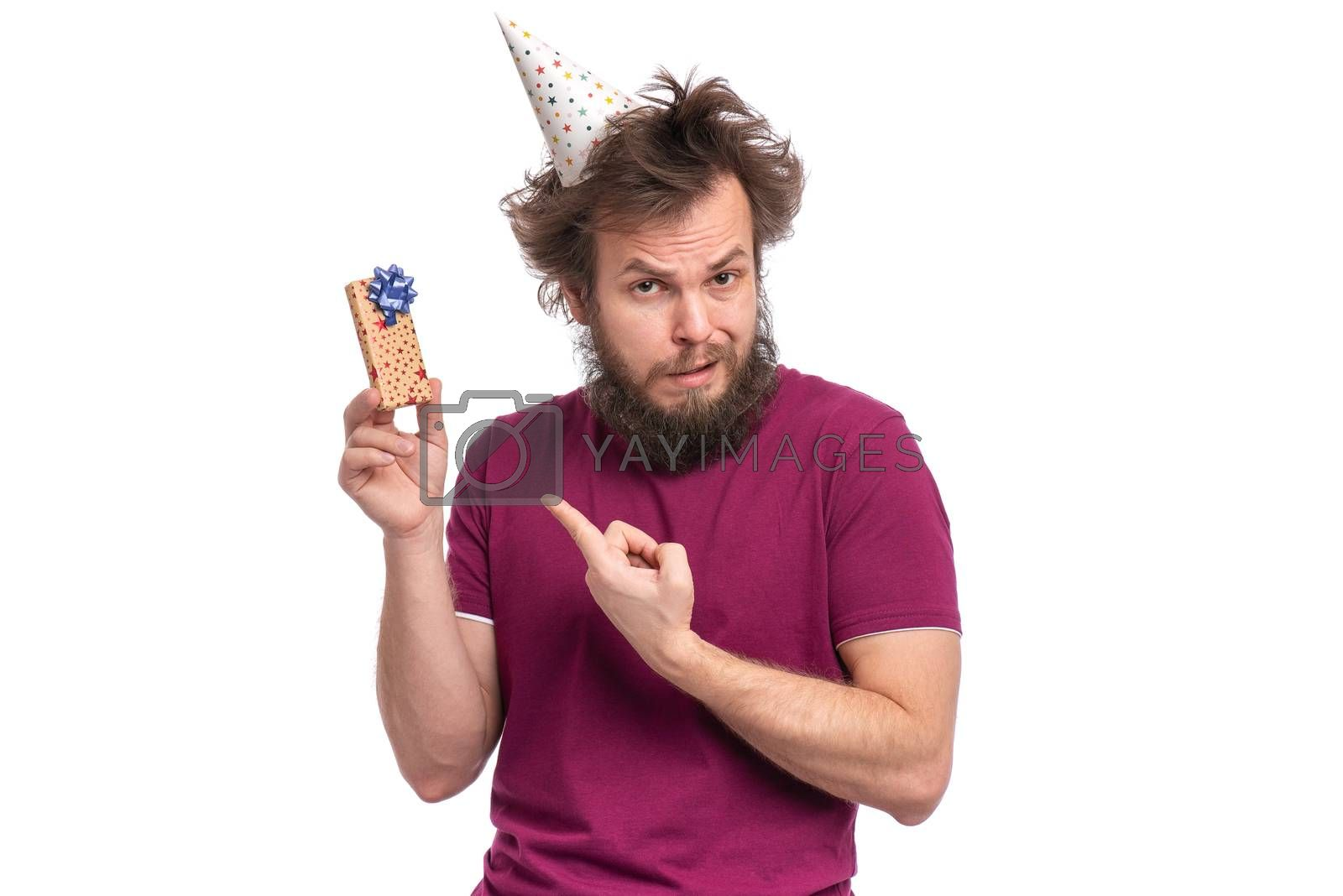 Crazy bearded Man with funny Haircut in birthday cap holding small gift box, isolated on white background. Surprised sad guy dissatisfied with his present. Holidays concept.