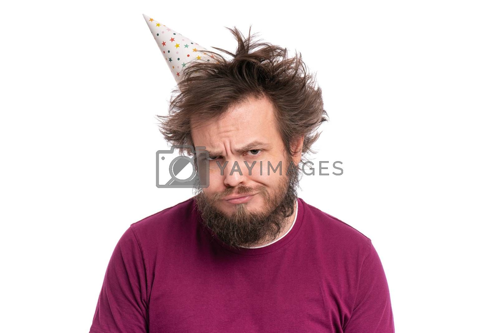 Crazy bearded Man with funny Haircut in birthday cap, isolated on white background. Unappy guy makes Offended Upset grimace. Holidays, Emotions and Signs concept.