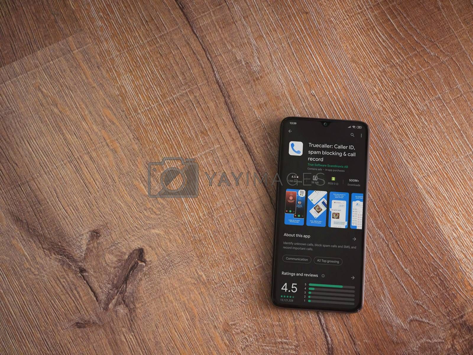Lod, Israel - July 8, 2020: Truecaller app play store page on the display of a black mobile smartphone on wooden background. Top view flat lay with copy space.