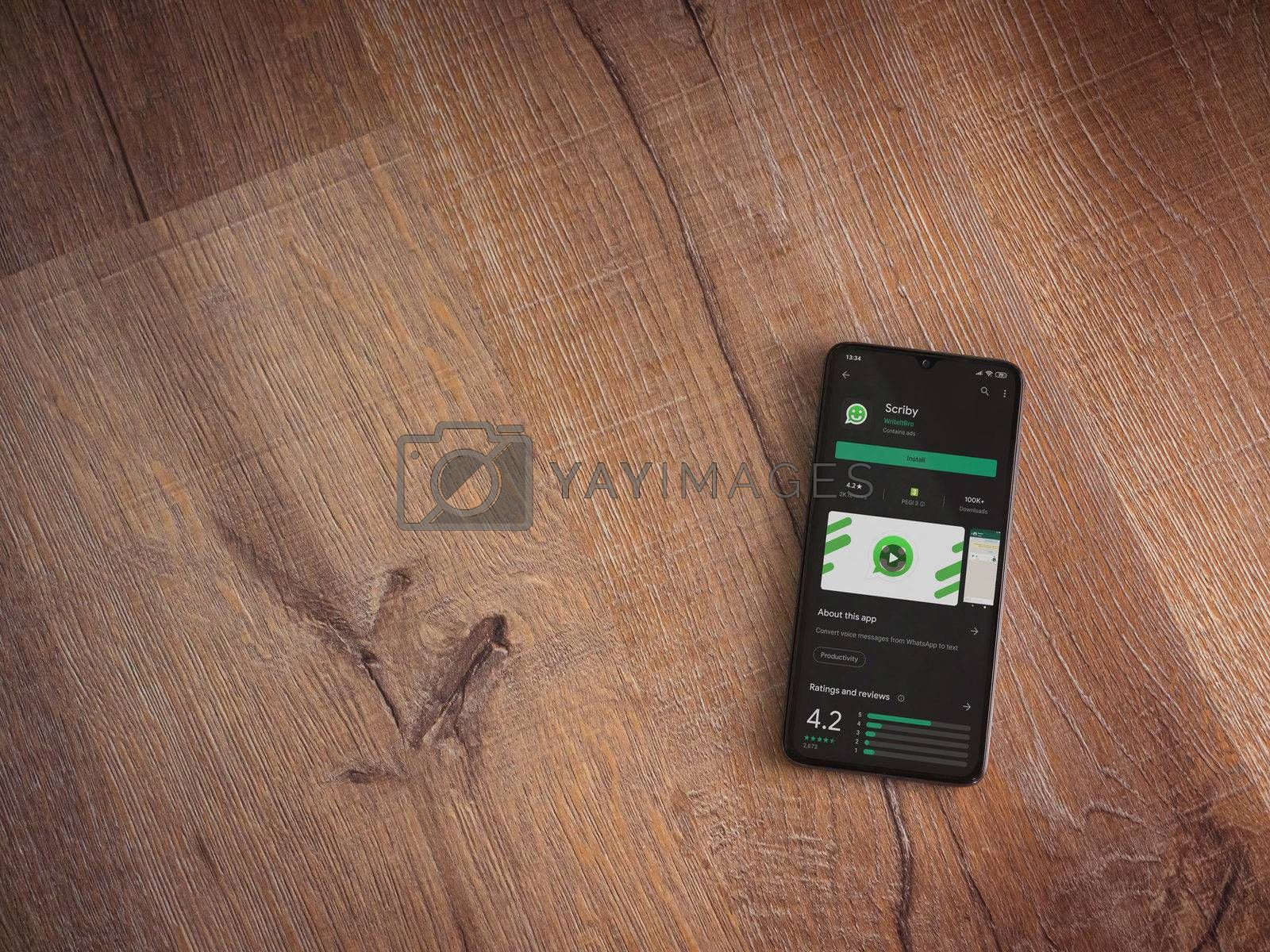 Lod, Israel - July 8, 2020: Scriby app play store page on the display of a black mobile smartphone on wooden background. Top view flat lay with copy space.