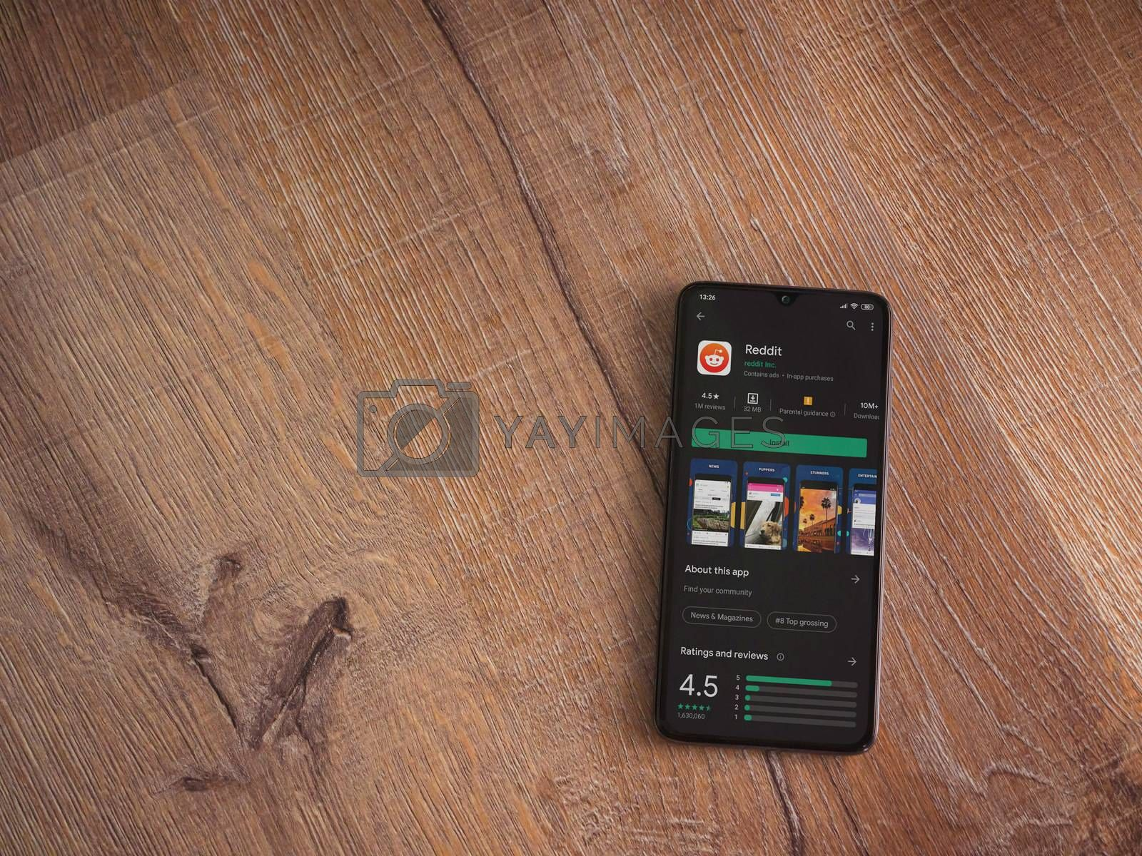 Lod, Israel - July 8, 2020: Reddit app play store page on the display of a black mobile smartphone on wooden background. Top view flat lay with copy space.