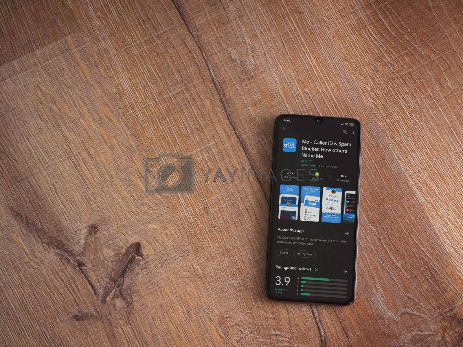 Lod, Israel - July 8, 2020: Me app play store page on the display of a black mobile smartphone on wooden background. Top view flat lay with copy space.