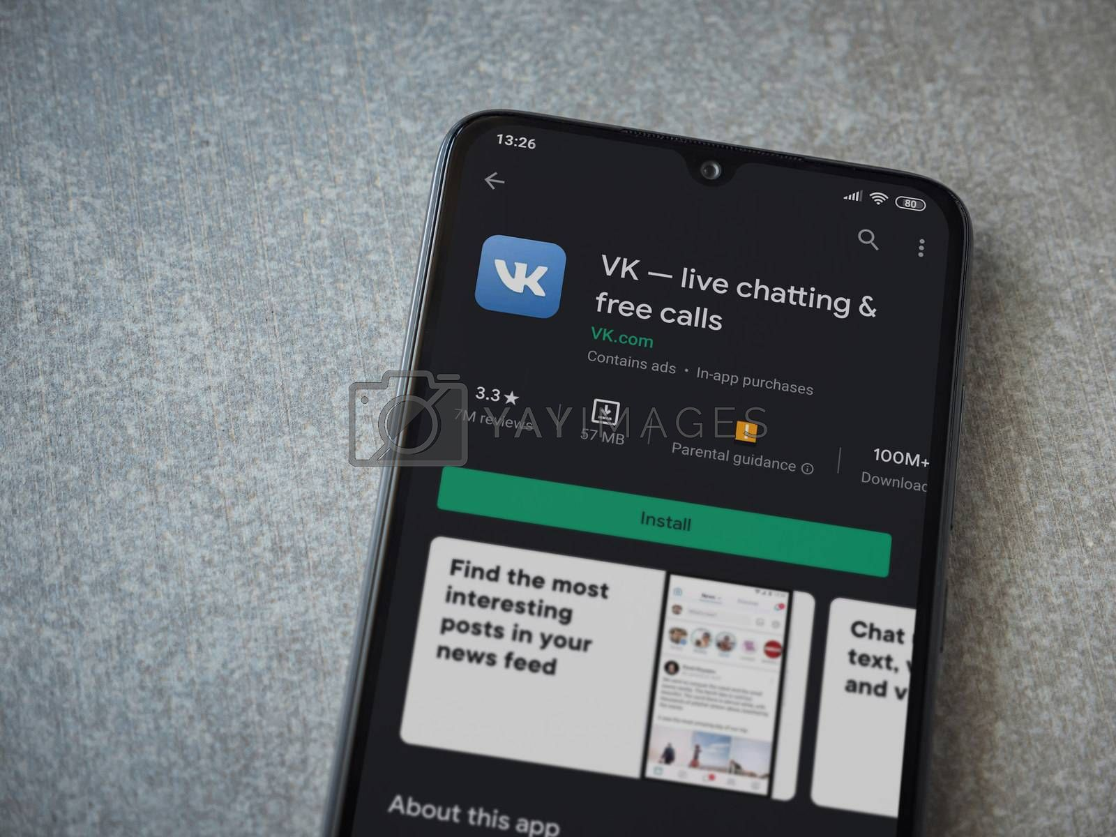 Lod, Israel - July 8, 2020: VK app play store page on the display of a black mobile smartphone on ceramic stone background. Top view flat lay with copy space.