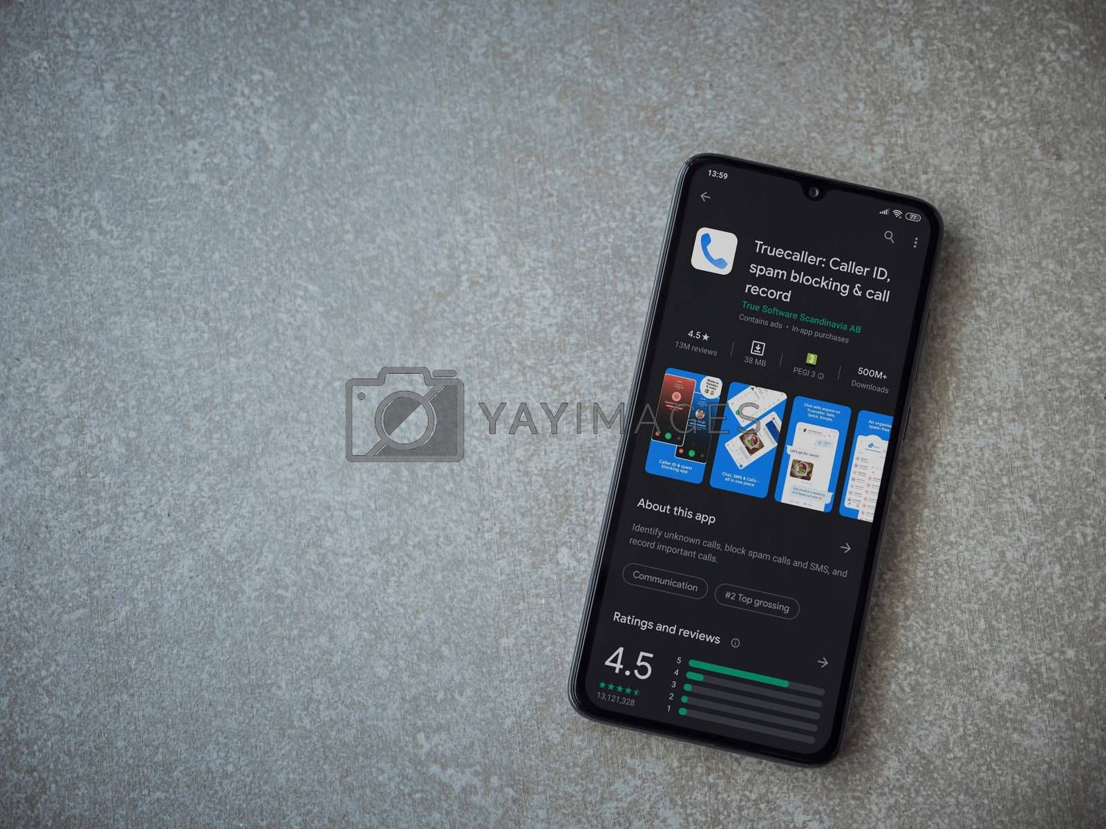 Lod, Israel - July 8, 2020: Truecaller app play store page on the display of a black mobile smartphone on ceramic stone background. Top view flat lay with copy space.