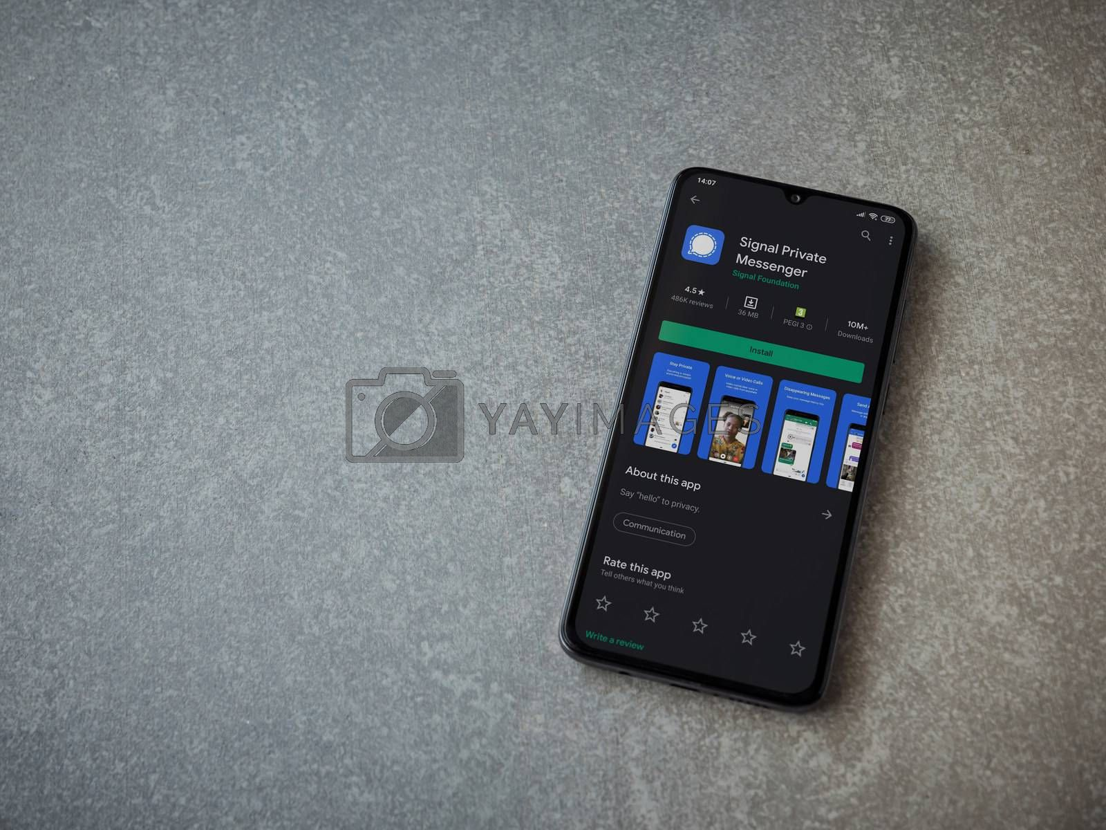 Lod, Israel - July 8, 2020: Signal Private Messenger app play store page on the display of a black mobile smartphone on ceramic stone background. Top view flat lay with copy space.