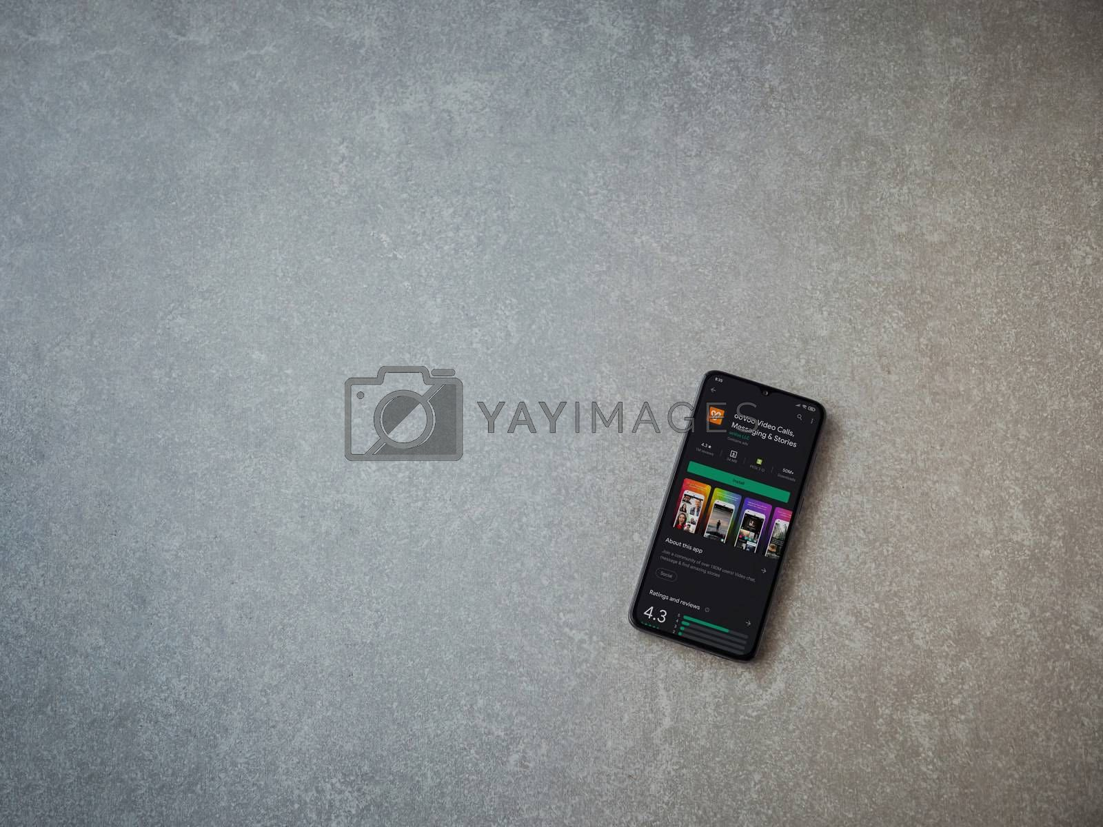 Lod, Israel - July 8, 2020: ooVoo app play store page on the display of a black mobile smartphone on ceramic stone background. Top view flat lay with copy space.