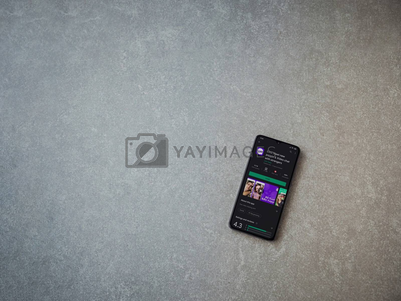 Lod, Israel - July 8, 2020: LiveU app play store page on the display of a black mobile smartphone on ceramic stone background. Top view flat lay with copy space.