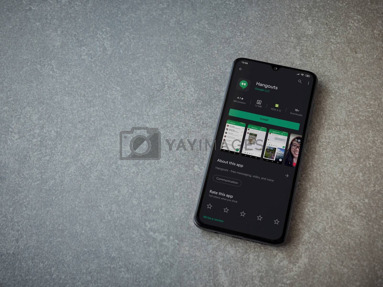 Lod, Israel - July 8, 2020: Hanghouts app play store page on the display of a black mobile smartphone on ceramic stone background. Top view flat lay with copy space.