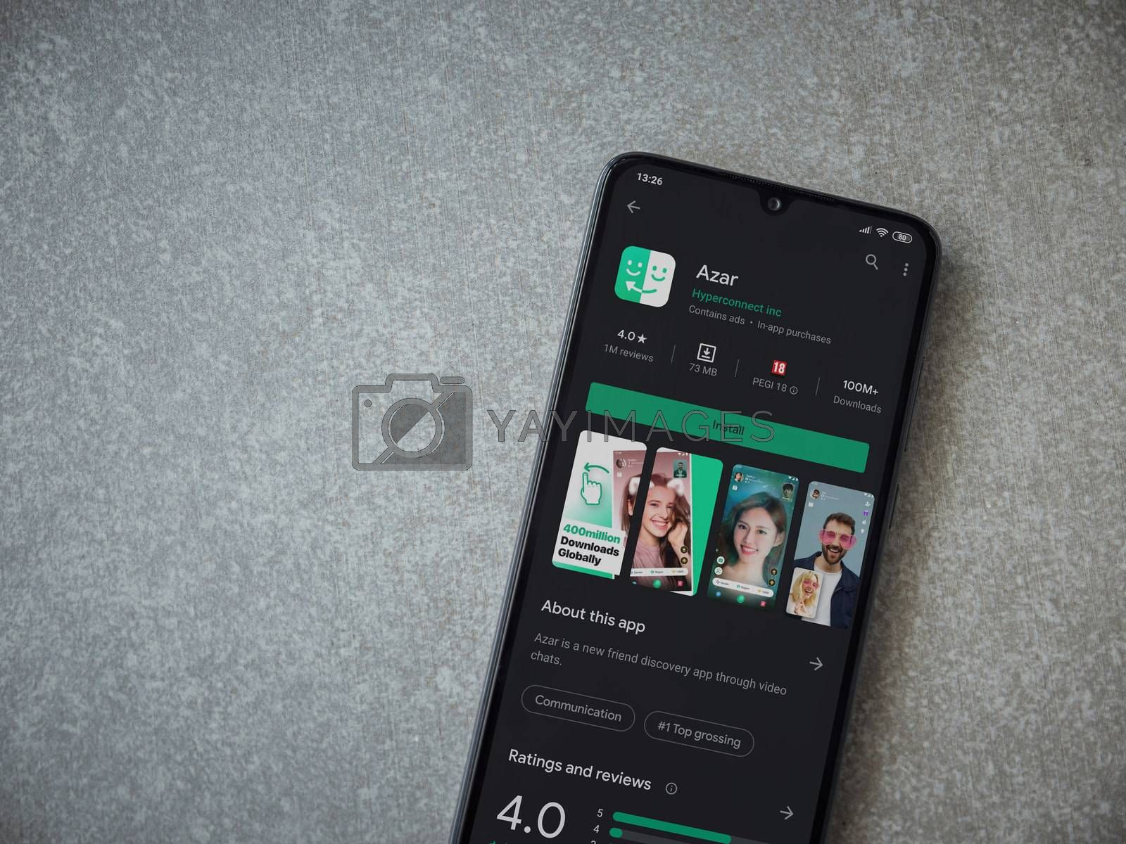 Lod, Israel - July 8, 2020: Azar app play store page on the display of a black mobile smartphone on ceramic stone background. Top view flat lay with copy space.