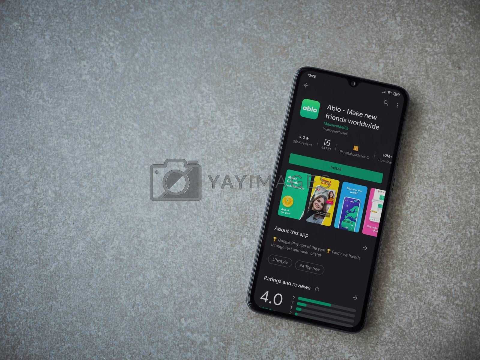 Lod, Israel - July 8, 2020: Ablo app play store page on the display of a black mobile smartphone on ceramic stone background. Top view flat lay with copy space.