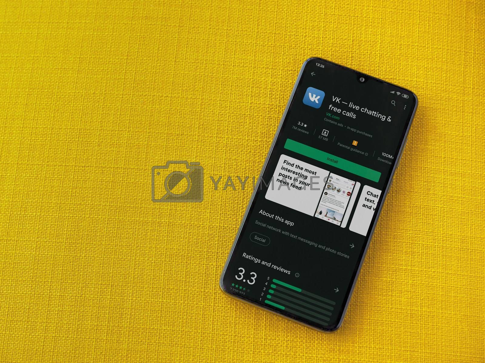 Lod, Israel - July 8, 2020: VK app play store page on the display of a black mobile smartphone on a yellow fabric background. Top view flat lay with copy space.