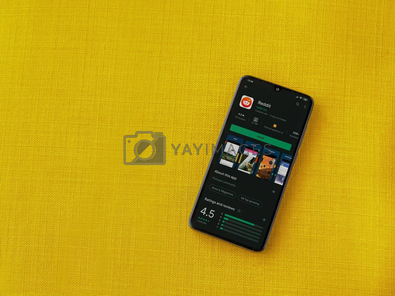 Lod, Israel - July 8, 2020: Reddit app play store page on the display of a black mobile smartphone on a yellow fabric background. Top view flat lay with copy space.
